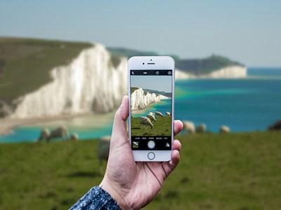Hand håller upp mobiltelefon som filmar kustlandskapet bakom