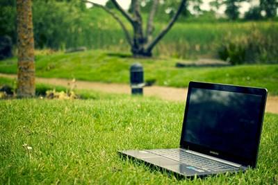 En öppen bärbar dator på gräsmatta