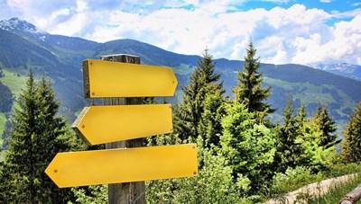 Vy över skog och berg. I förgrunden finns en stolpe med gula skyltar som pekar åt olika håll. Fotografi.